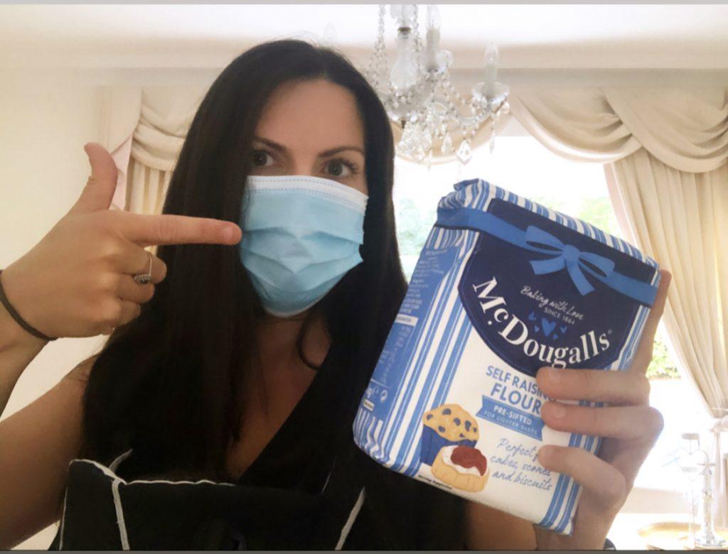 Woman wearing mask holding flour